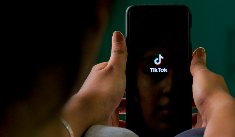 A mobile user browses through the Chinese owned video-sharing 'Tik Tok' app on a smartphone | AFP