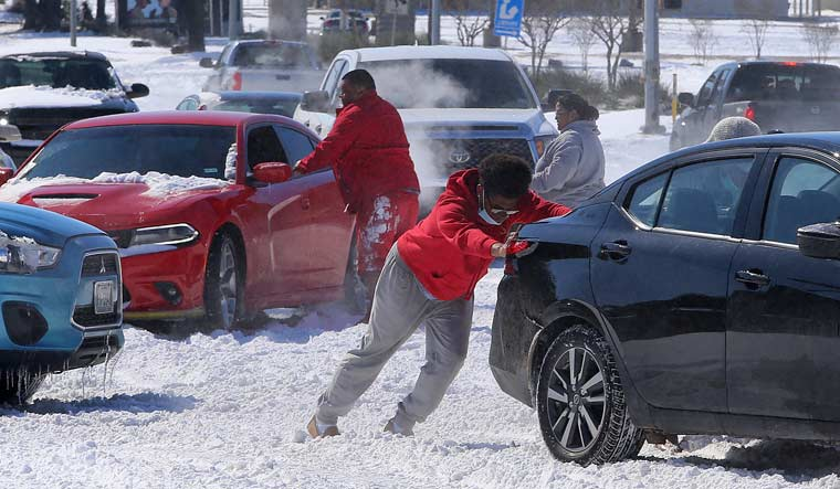 texas-winter-storm-cold-pushing-cars-ap