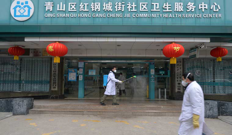 A doctor disinfects the entrance of a community health service center, which has an isolated section to receive patients with mild symptoms caused by the novel coronavirus and suspected patients of the virus, in Qingshan district of Wuhan | Reuters