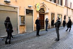 People wait at a distance from one another while waiting to buy take away pizza on Via delle Muratte in Rome | AFP